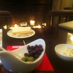 Olives and house-made Parmigiano-Reggiano popcorn by the fire while you wait for your table.