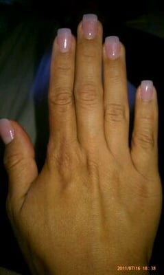 Natural acrylic nails with pink nail polish.