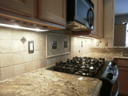 Backsplash with 2x2 impressions glass inserts from design materials