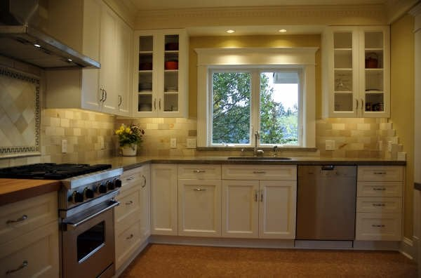 sunny yellow paint and gold tile created a cheery and inviting kitchen