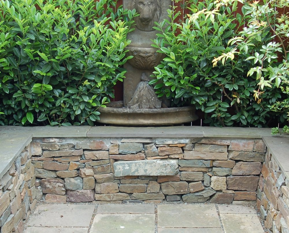 Drystack stone wall with bench top. Flagstone patio courtyard. | Yelp