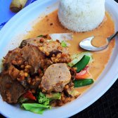 Crispy Duck served in a Panang Curry Sauce with rice and vegetables.