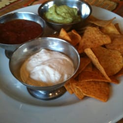 Three dips: tortilla chips, salsa, guacamole, and sour cream