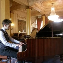 A wedding pianist playing the piano for a drinks reception at Down Hall.