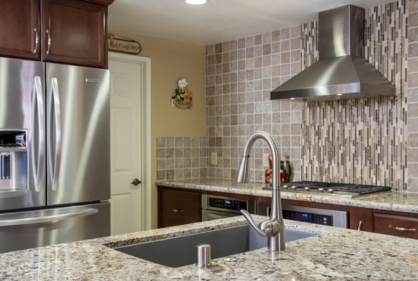 Unique vertical stove backsplash with stainless appliances and fixtures.